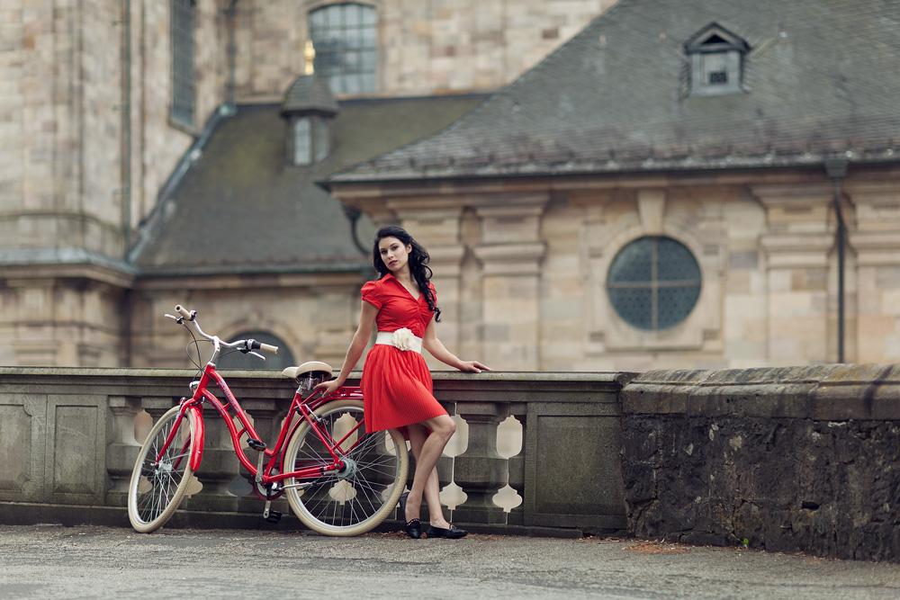 Natalie mit einem roten Fahrrad vor dem Fuldaer Dom
