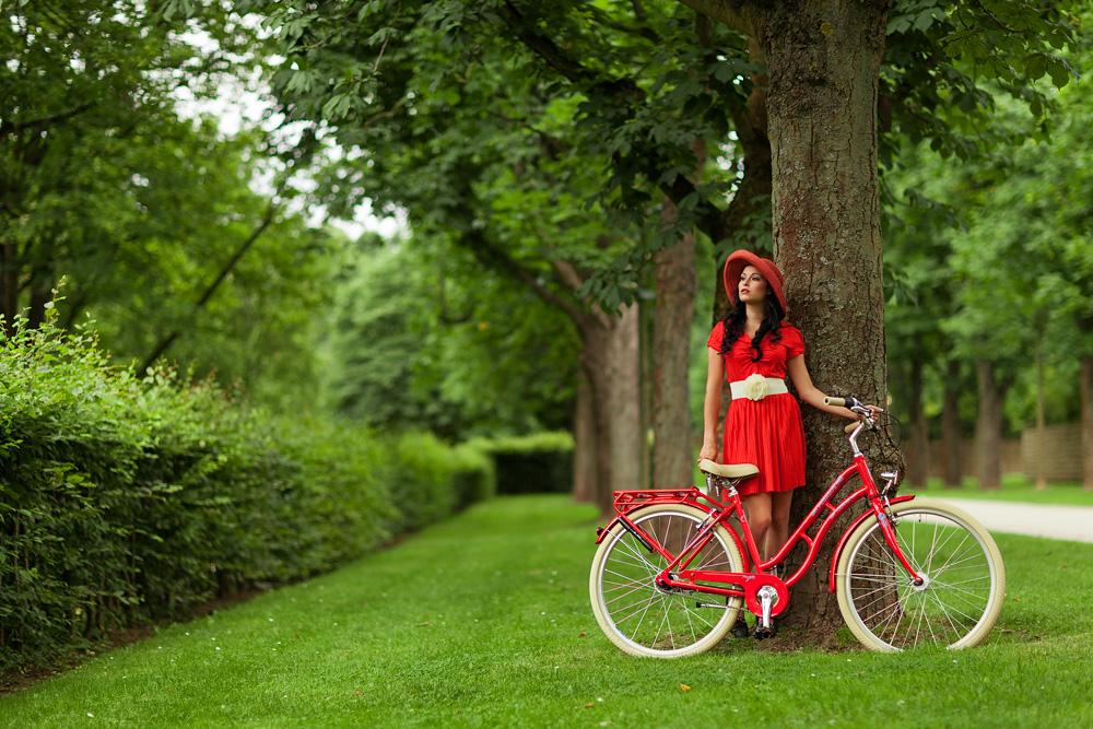 Natalie im Schlosspark, mit einem roten Fahrrad