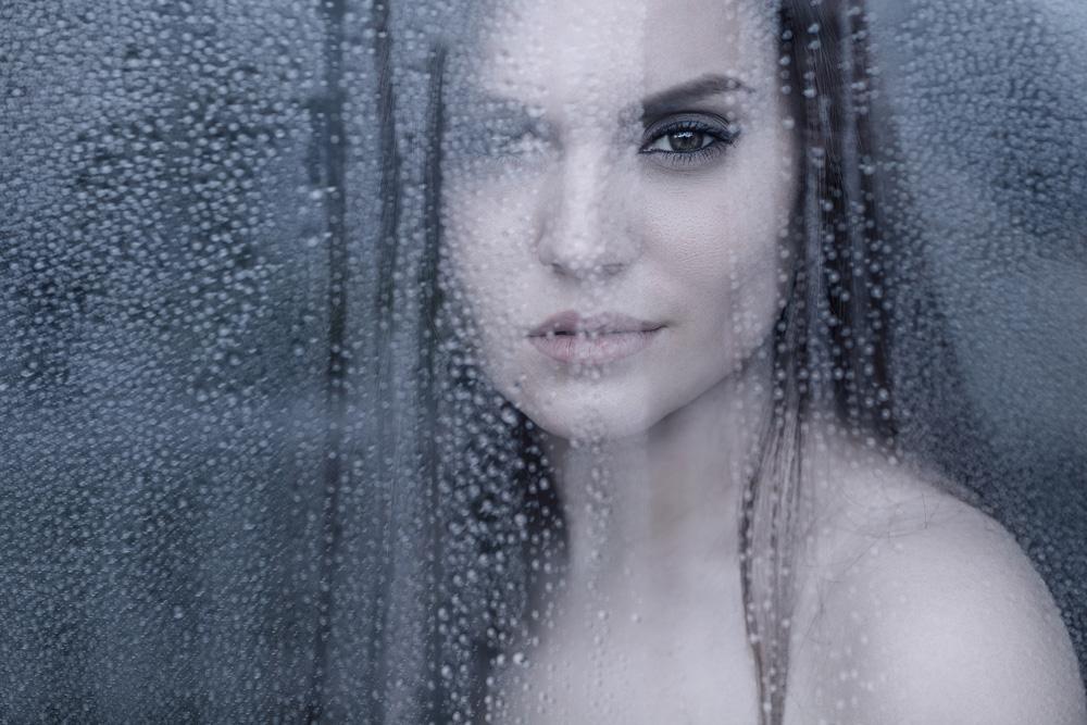Portrait von Anna, durch eine Scheibe mit Regentropfen